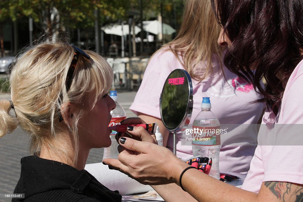 Make up artists apply lip gloss to donors at the ULTA Beauty's Kiss Kart which supports The Breast Cancer Research Foundation at Klyde Warren Park on October 17, 2013 in Dallas, Texas.
