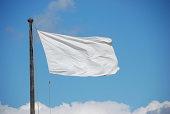 White flag against blue sky.
