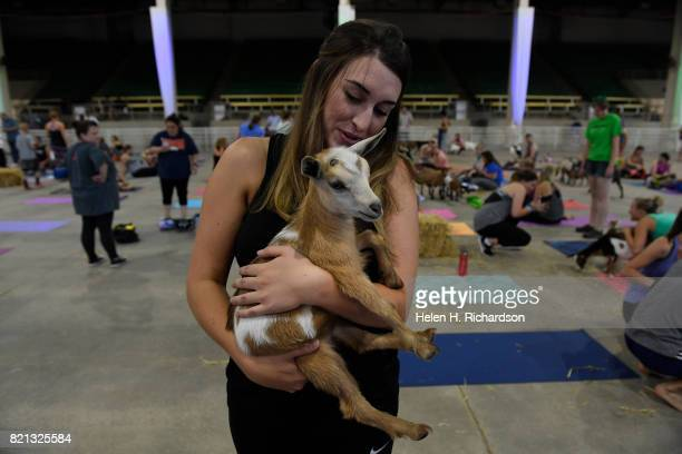 Makenzie Love holds a baby goat after goat yoga at the Denver County Fair on July 23 2017 in Denver Colorado 236 yogis turned out to do yoga with 52...