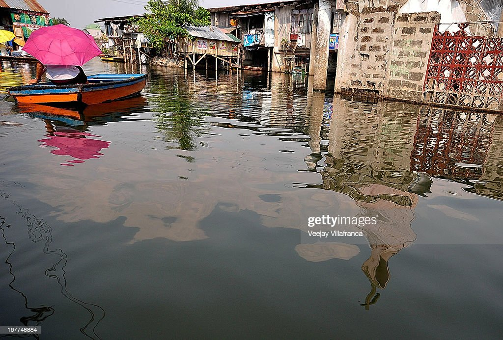 Makeshift boats wade through the waterways in Artex Compound in Malabon City on April 28, 2013 in Manila, Philippines. The residents of the former textile compound had to adjust their daily lives after flood waters submerged their low-lying village in 2004.