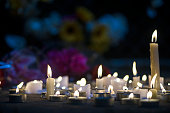 A growing makeshift vigil for victims made out of various size candles on a concrete sidewalk at night with flowers and some flowers stuck in the chainlink fence in the background. These types of memo