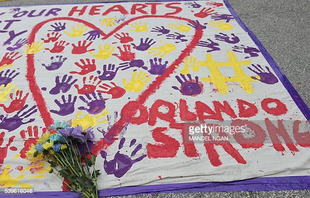 A makeshift memorial with flowers and hand prints is seen in a parking lot near the Pulse nightclub in Orlando Florida on June 12 2016 A somber...