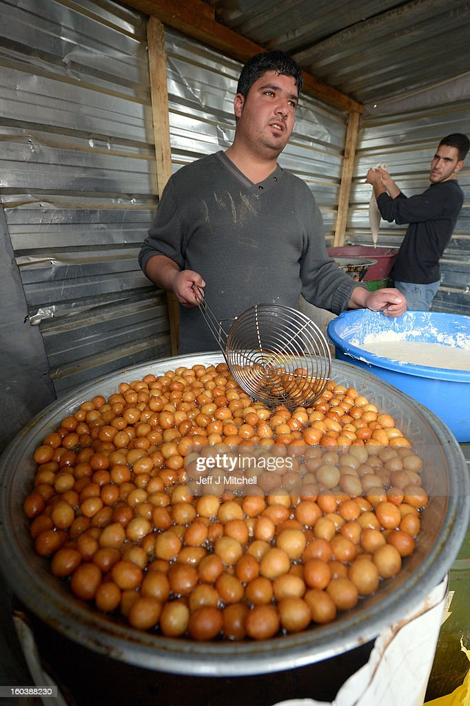 ZA'ATARI, JORDAN - JANUARY 30: Makeshift shops sell produce in the main thoroughfare as Syrian refugees go about their daily business in the Za'atari refugee camp on January 30, 2013 in Za'atari, Jordan. Record numbers of refugees are fleeing the violence and bombings in Syria to cross the borders to safety in northern Jordan and overwhelming the Za'atari camp. The Jordanian government are appealing for help with the influx of refugees as they struggle to cope with the sheer numbers arriving in the country.