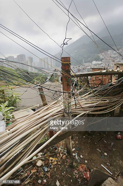 Makeshift water and other utility lines run in the Rocinha community or favela with the wealthy neighborhood of Sao Conrado in the distance on...