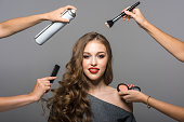 Makeup and hairstyle process, portrait of beautiful young woman and many hands with a brush, powder, comb and hairspray. Studio shot, gray background