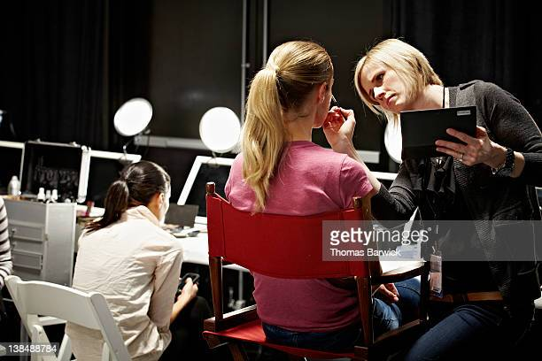 Make-up artist and model backstage at fashion show