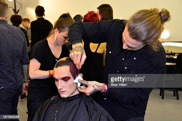 A makeup artist applies color to a model's hair backstage during Siki Im during Fall 2013 MercedesBenz Fashion Week at Cafe Rouge on February 12 2013...
