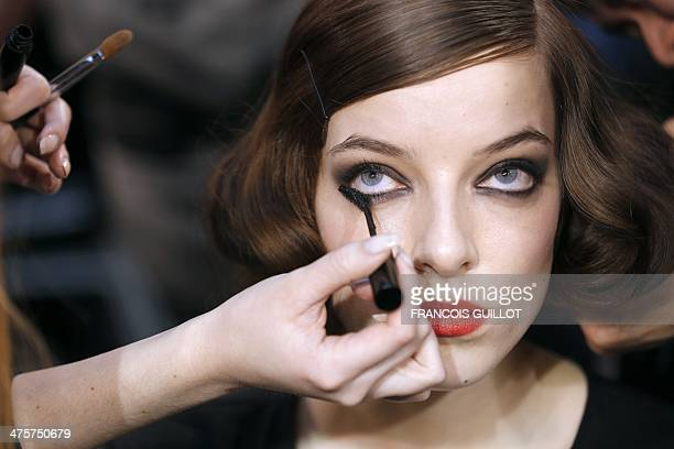 A makeup artist applies makeup on a model backstage prior to the start of the Tsumori Chisato 2014/2015 Autumn/Winter readytowear collection fashion...