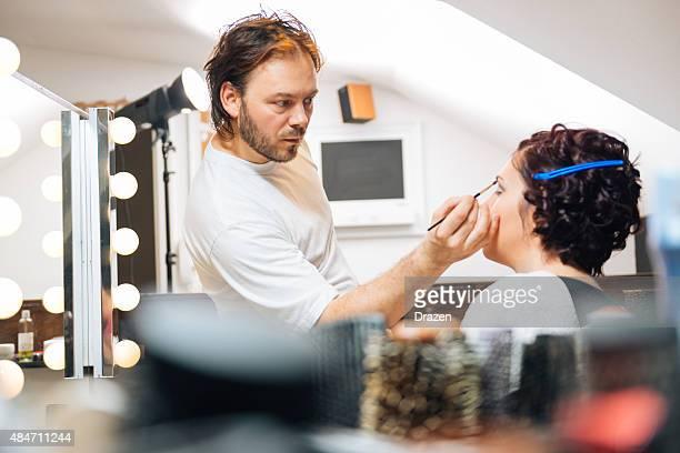 Maquilleuse applique mascara sur Belle femme dans un studio photo