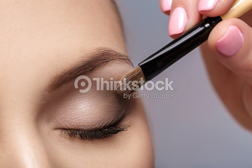 makeup artist apply makeup brush for eyes. makeup for young girl. brown eye shadow
