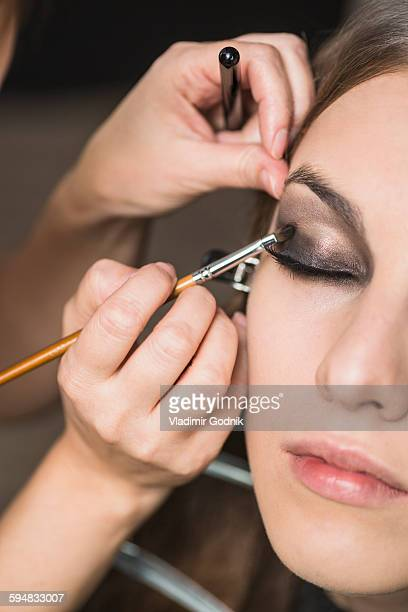Make-up artist applying eyeshadow on fashion model