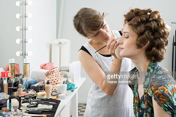 A make-up artist applying make-up on a model