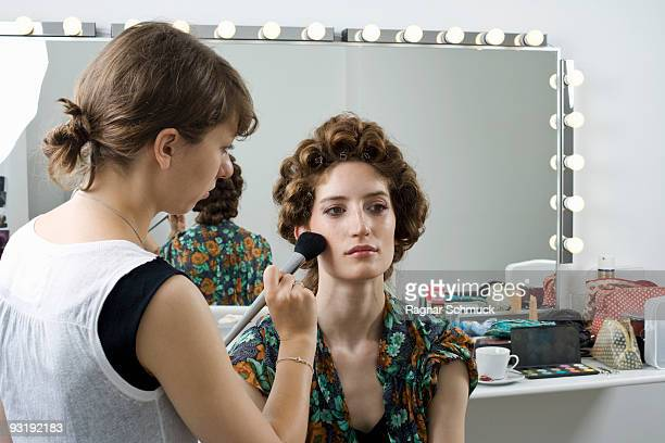 A make-up artist applying make-up on a model