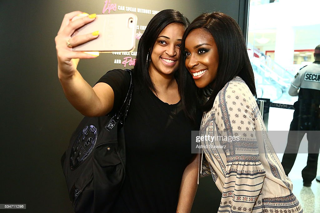 Makeup artist Jackie Aina (right) takes a selfie with a fan NYX Professional Makeup Store Kings Plaza Ribbon Cutting on May 25, 2016 in Brooklyn, New York.