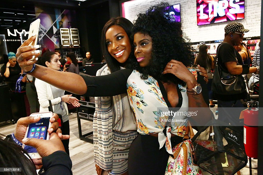 Makeup artist Jackie Aina (left) takes a selfie with a fan NYX Professional Makeup Store Kings Plaza Ribbon Cutting on May 25, 2016 in Brooklyn, New York.