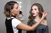 Makeup process, makeup artist using brush and compact powder and colors model at salon. Portrait of two beautiful women