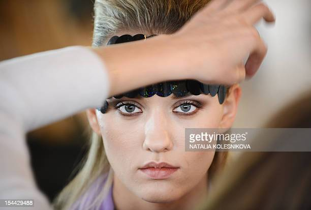 A makeup artist prepares a model backstage before a show during the Russian Fashion Week in Moscow on October 19 2012 AFP PHOTO / NATALIA KOLESNIKOVA