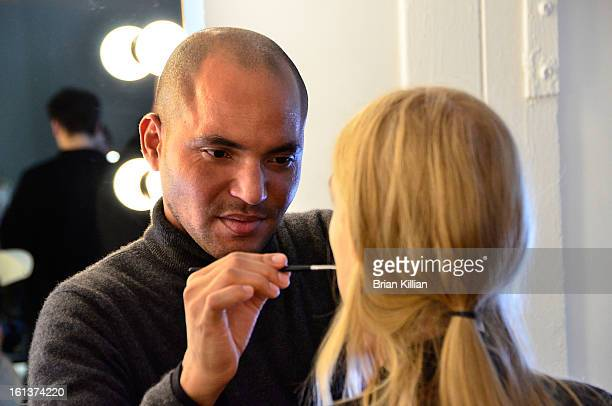 A makeup artist prepares a model during the Jeremy Laing during Fall 2013 MercedesBenz Fashion Week at Pier 59 Studios on February 10 2013 in New...