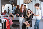 Make-up artist preparing beautiful female model for fashion show