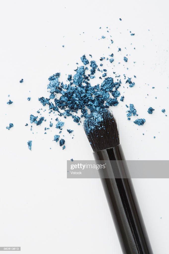 Make-up brush with blue eyeshadow on white background