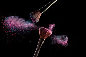Make-up brushes with pink and blue powder explosion on black background