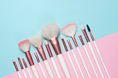 Set of makeup brushes on pink and aqua colored composed background. Top view point, flat lay.