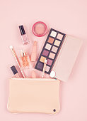 Mockup of makeup cosmetic products over pastel pink background, flat lay, top view. Woman beauty fashion decorative.