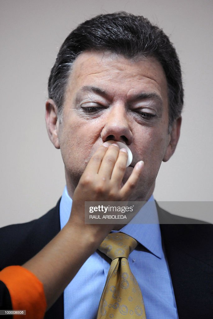 Make-up is applied to Juan Manuel Santos (R), presidential candidate for the ruling Partido de la U (The U party) prior to a debate in Medellin, Antioquia department, Colombia on May 13, 2010. Colombia will hold their presidential elections first round next May 30, and polls show a face-off for a second round on June 20 between Green Party candidate Antanas Mockus and the ruling Partido de la U candidate Juan Manuel Santos, a former Defense minister. AFP PHOTO/Raul ARBOLEDA