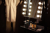 Beautician cosmetics on small table near mirror with light bulbs in dressing room