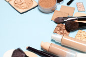 Makeup products for creating the perfect skin tone: concealer, primer, liquid foundation fluid with correcting, bronzing, golden shimmer, highlighting make-up powder. Copy space