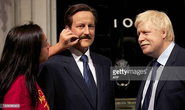 A makeup technician adjusts the moustaches on the wax figure of British Prime Minister David Cameron and Mayor of London Boris Johnson at Madame...