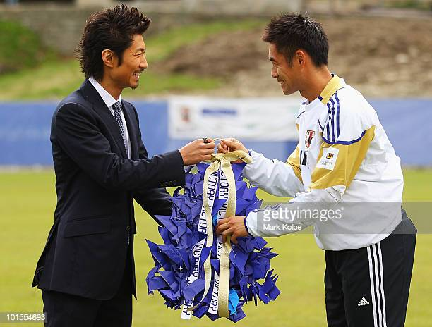 Makidai of the allmale Japanese pop band and dance group Exile presents a gift to Yoshikatsu Kawaguchi during a visit to a Japan training session at...