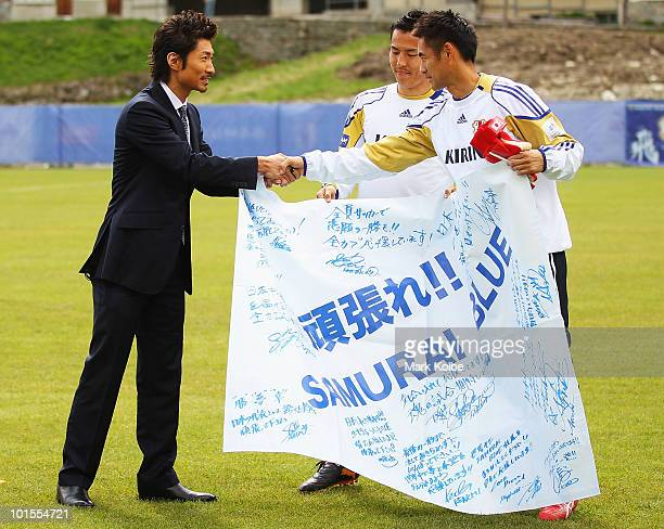 Makidai of the allmale Japanese pop band and dance group Exile presents a banner to Yoshikatsu Kawaguchi during a visit to a Japan training session...