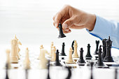 Hand of businessman playing chess: strategy and tactics in business