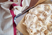 Cooking the meringue base for a Pavlova dessert. Fresh meringue, with crisp golden top, on baking parchment and a stainless steel baking tray. Overhead view on wooden table with cloth.