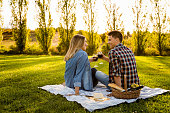 Shot of a happy couple enjoying a day in the park and making a toast