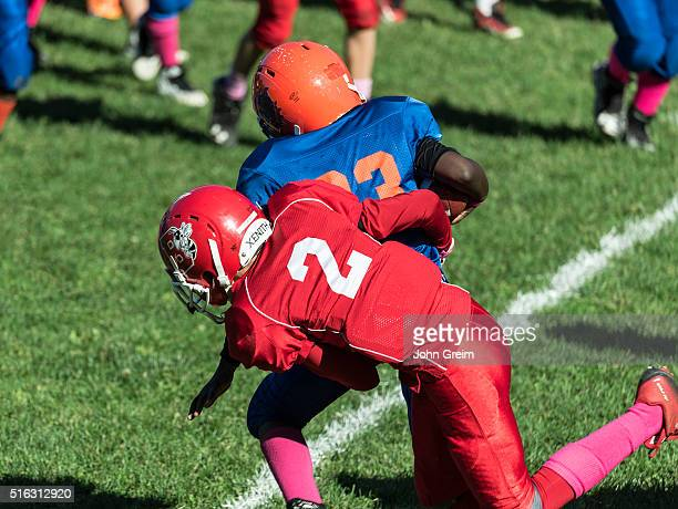 Making a tackle during a Pop Warner football game