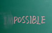 Changing the word impossible to possible on chalkboard.