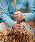 Child stirring Christmas pudding mixture with a wooden spoon.
