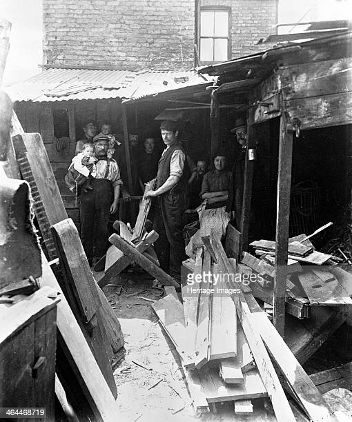 Making firewood from scrap timber 1900s The workers and their families are in a delapidated yard with a makeshift corrugated iron roof surrounded by...