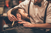 Close-up side view of young bearded man getting shaved with straight edge razor by hairdresser at barbershop