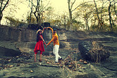 Young couple of Indian ethnicity making a love symbol on rock.