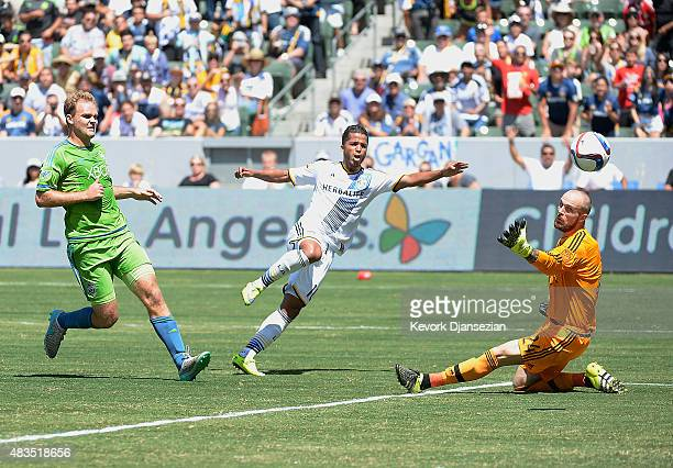 Making his MLS debut Giovani Dos Santos of the Los Angeles Galaxy scores a goal against goalkeeper Stefan Frei and Chad Marshall of the Seattle...