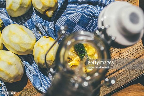 Making limoncello. Pouring alcohol on lemon peel