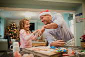 Little girl is having fun making christmas biscuits with her dad. He is playfully flicking icing powder at her.