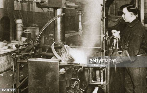 Making money lowering a pot of liquid metal into a machine 20th century