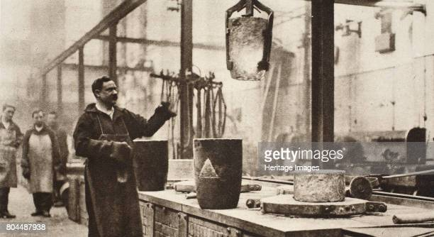 Making money pots of liquid metal being handled in the melting room 20th century A red hot pot containing liquid metal has been lifted out of the...