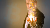 making money with bitcoin - Business man creating bitcoins with his hand