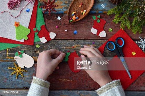 Fabricación de juguetes de Navidad hecha a mano de fieltro con sus propias manos. Concepto de DIY de los niños. Hacer decoración de árbol de Navidad o tarjetas de felicitación. Paso 3. Decorar el juguete : Foto de stock