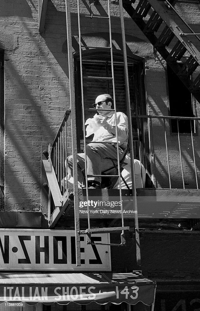 Making of movie The Godfather on Mott Street in Manhattan Movie watcher sits on fire escape eating his lunch and watches making of the film
